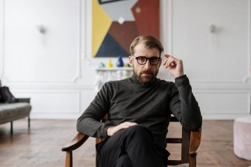 man in black sweater sitting on brown wooden chair