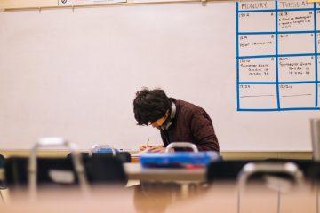 man writing on table