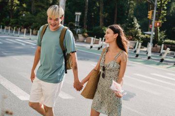 happy diverse couple strolling on crosswalk